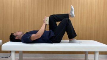 体幹を屈曲させ(カールアップ)、片方の股関節を90°屈曲位にします。 両手を膝上に添える、またはハーフポールなどで抑えます。そしてもう片方の下肢を伸展位にします。